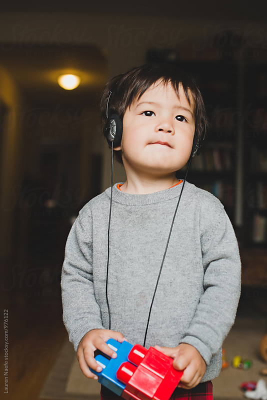 Little kid listening to music on headphones by Lauren Naefe for Stocksy United