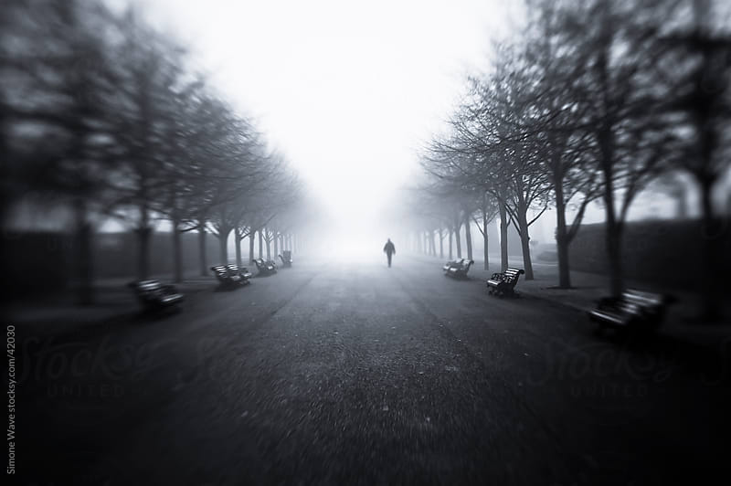 Lonely man walking in the fog by Simone Becchetti for Stocksy United