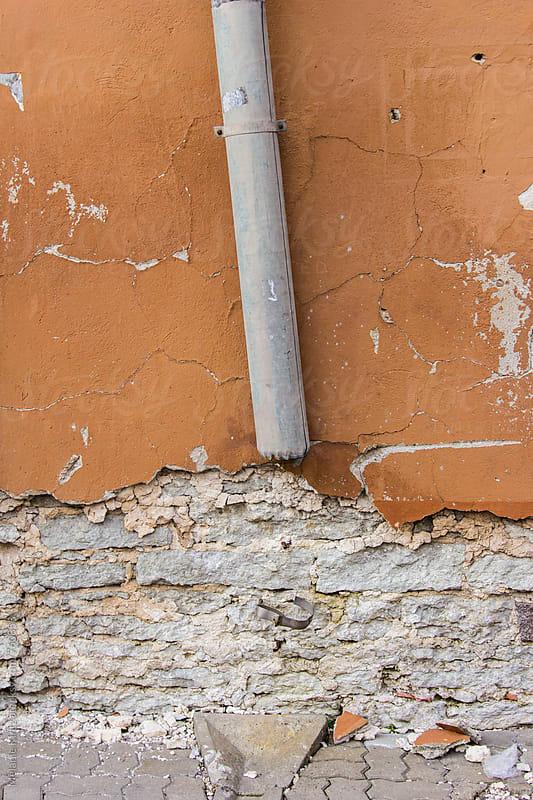 Broken Rain gutter on wall by Melanie Kintz for Stocksy United