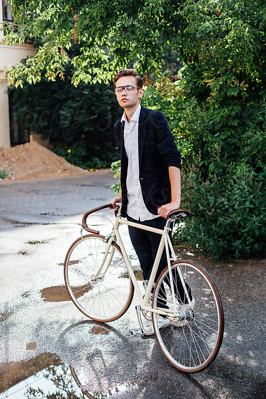 Young hipster man posing outdoor with bicycle by Viktor Solomin for Stocksy United