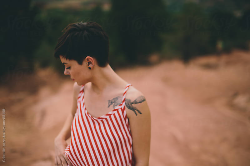 Edgy girl profile in striped shirt outdoors by Gabrielle Lutze for Stocksy United