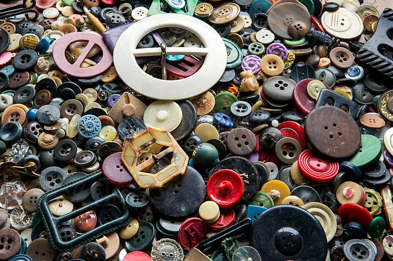 Antique and vintage buttons and buckles laid out on a table by Paul Phillips for Stocksy United