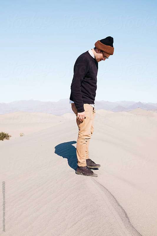 young fashionable male on top of sand dune ridge  by Jesse Morrow for Stocksy United