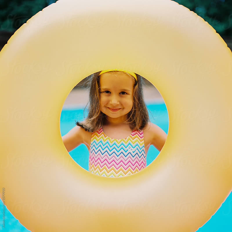 Cute young girl with a big inter tube standing by a swimming pool by Jakob for Stocksy United