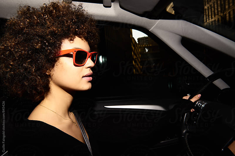 Side view of young woman in sunglasses driving a car by Guille Faingold for Stocksy United