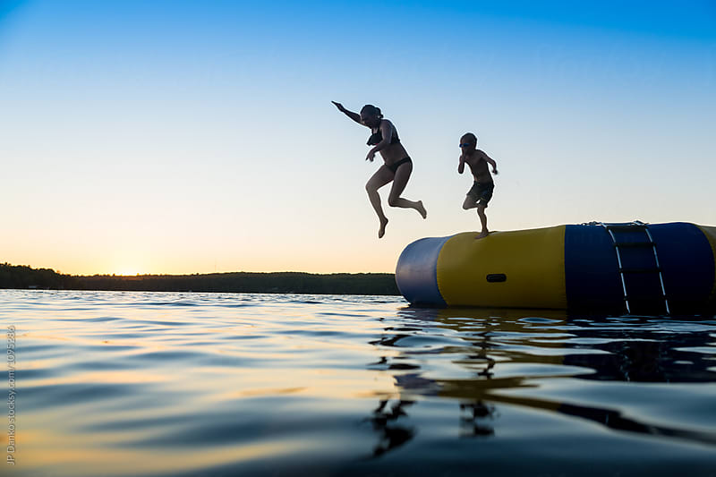 Woman and Boy Jumping Into Warm Summer Cottage Lake At Sunset from Dock by JP Danko for Stocksy United