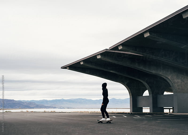 Woman riding away on skateboard by Isaiah & Taylor Photography for Stocksy United