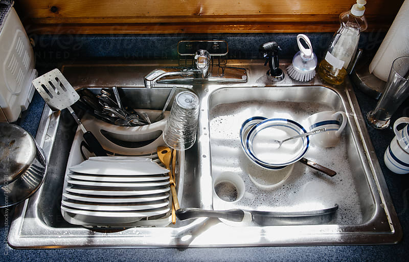 Sink filled with dishes and soapy water by Cara Dolan for Stocksy United