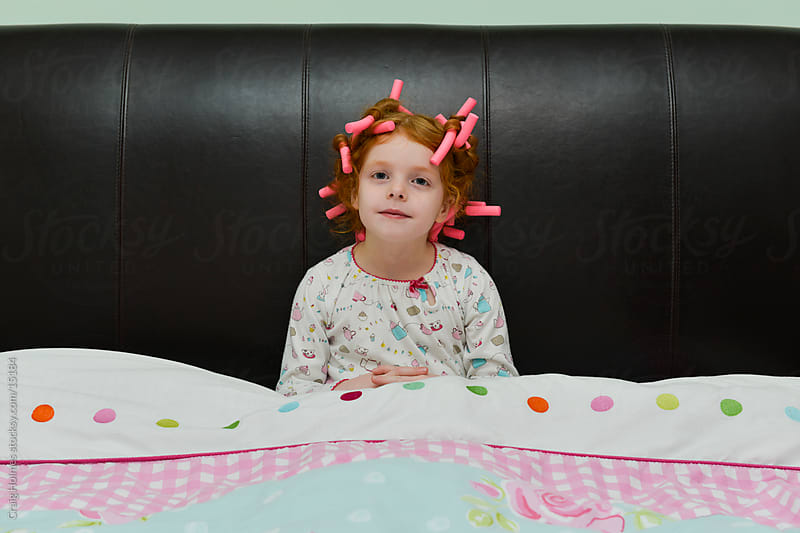 6 year old girl sat in bed with pink bendy hair rollers by Craig Holmes for Stocksy United