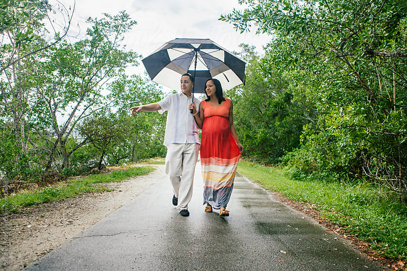 Couple Holding Umbrella on Boardwalk by Stephen Morris for Stocksy United