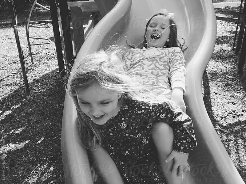 Two girls laugh while riding tandem down a slide. by Kelsey Gerhard for Stocksy United