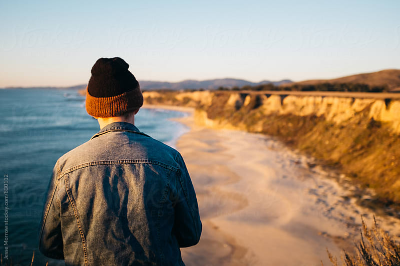 young male looking away from camera at coast line cliff and ocean by Jesse Morrow for Stocksy United