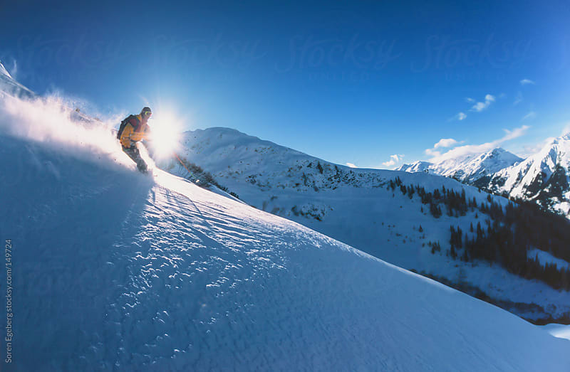 Man skiing powder snow in winter mountains backlit by the sun. by Soren Egeberg for Stocksy United