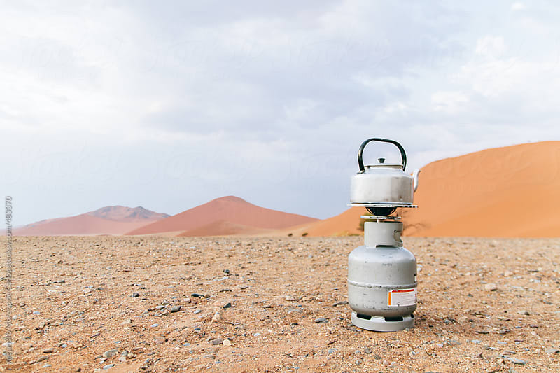 Teapot on top of a camping gas stove gas cooker in the middle of the desert by Alejandro Moreno de Carlos for Stocksy United