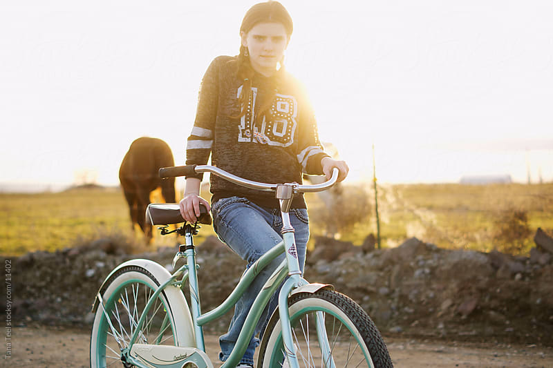 A young teen girl stands with her bicycle on a dirt road. by Tana Teel for Stocksy United