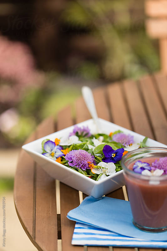 Light lunch of salad with flower in the garden by Kirsty Begg for Stocksy United