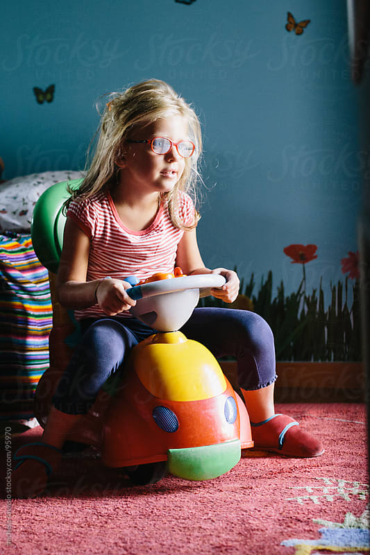 Little girl playing with a toy car, at home. by michela ravasio for Stocksy United