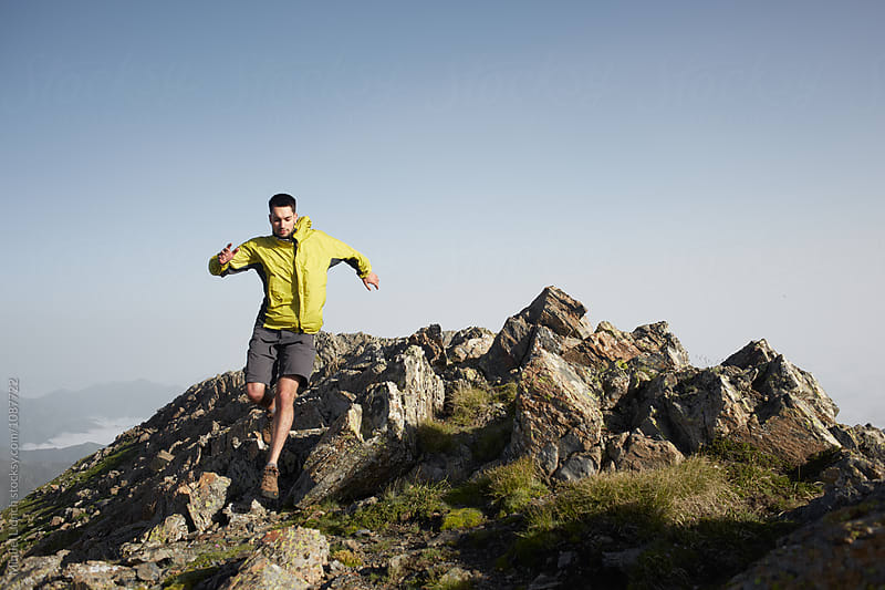 Young man running on the top of a mountain ridge by Miquel Llonch for Stocksy United