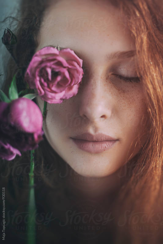 Portrait of a beautiful redhead with freckles holding a rose by Maja Topcagic for Stocksy United