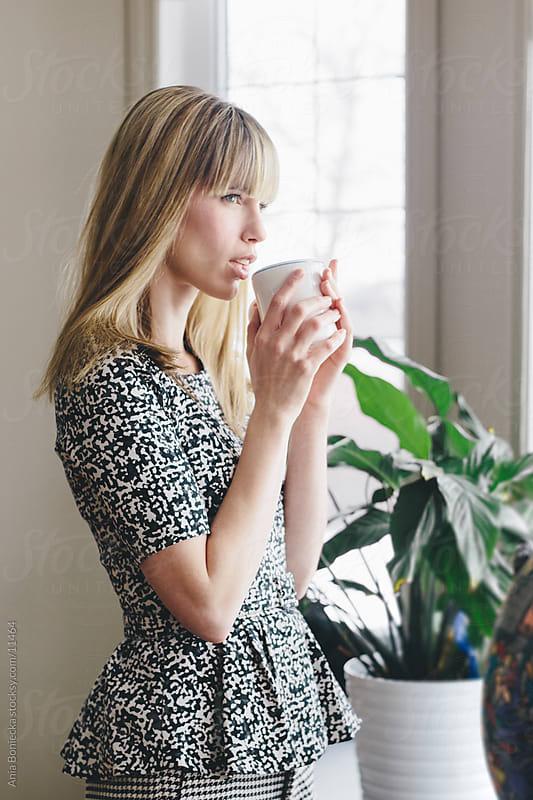 Beautiful woman drinking out of a mug by Ania Boniecka for Stocksy United