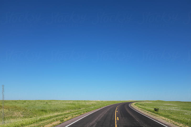 Two lane highway across the Great Plains of North America under a cloudless sky by David Smart for Stocksy United