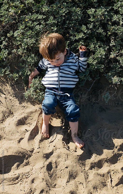 Child lays on the sand. by Lucas Saugen for Stocksy United