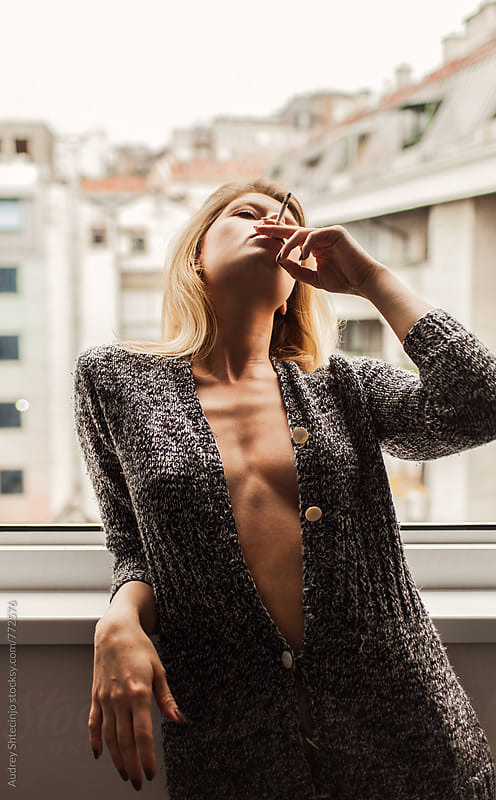 Portrait of sensual female on window smoking. by Audrey Shtecinjo for Stocksy United