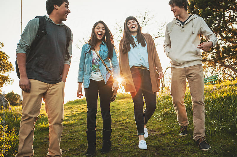 Group of teenage friends hanging out, laughing. by Rob and Julia Campbell for Stocksy United