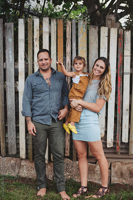Young, stylish family standing in front of funky fence in tropical neighbourhood by Rob and Julia Campbell for Stocksy United