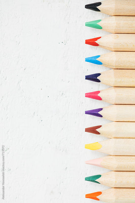 Set of colorful pencils against a white wooden background by Aleksandar Novoselski for Stocksy United