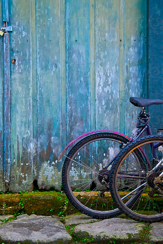 Bike outside an old blue painted wooden doored  by Jaydene Chapman for Stocksy United