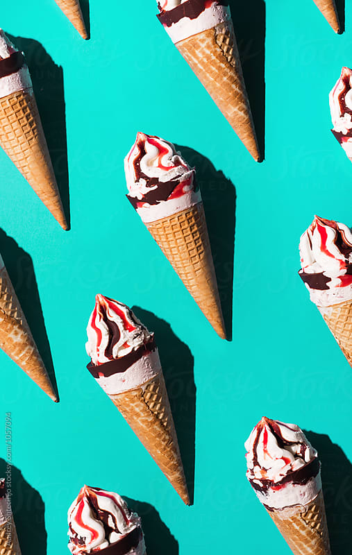 Strawberry / vanilla ice creams on cyan/blue background. by Marko Milanovic for Stocksy United