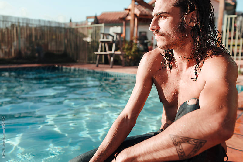 A wet tatooed man sits by the pool  by HOWL for Stocksy United