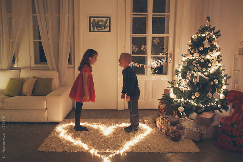 Brother and Sister Sharing Love on Christmas Eve by Lumina for Stocksy United