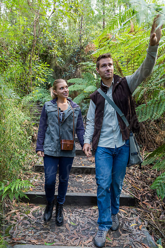 Young couple walking down a bush track by Ben Ryan for Stocksy United