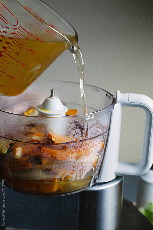 Pouring vegetable stock in a blender with roasted sweet potato and fennel. by Darren Muir for Stocksy United