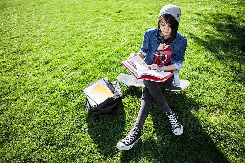 Asian college student studying on the grass outdoor by Suprijono Suharjoto for Stocksy United