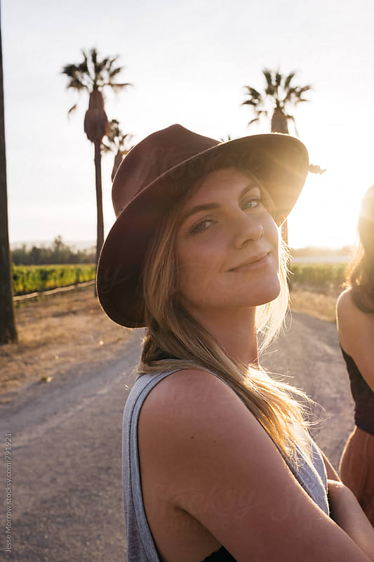 young woman wearing hat at sunset on california road by Jesse Morrow for Stocksy United