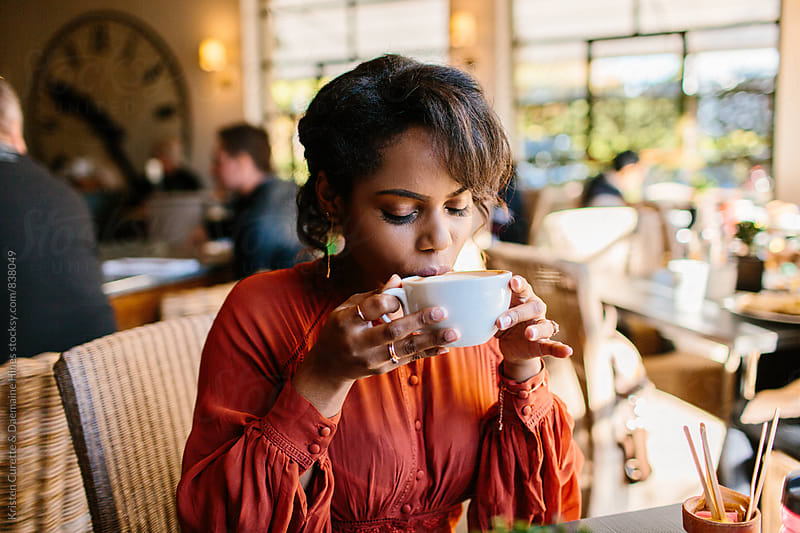 Beautiful woman sitting in a coffee shop sipping her latte  by Kristen Curette Hines for Stocksy United