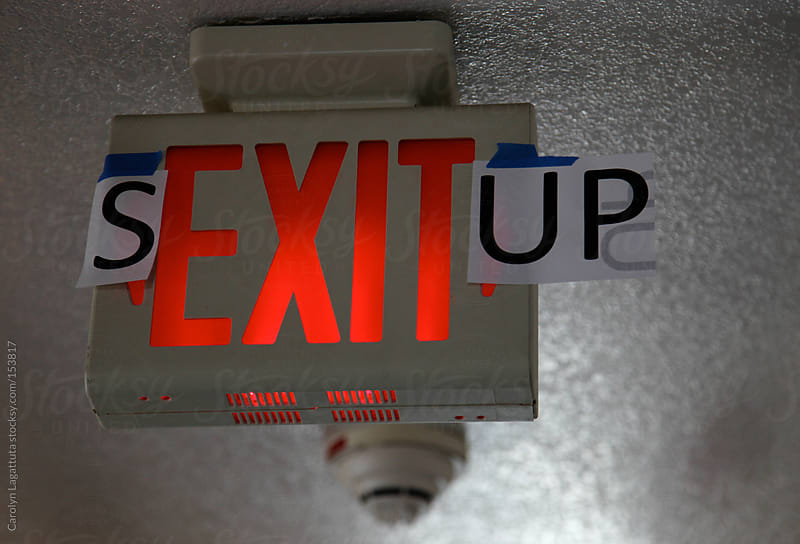 Exit sign with some added letters to spell Sex It Up in a college dorm hallway by Carolyn Lagattuta for Stocksy United