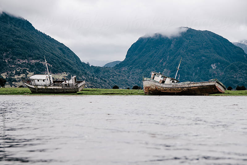 Two abandoned ships at Port Chacabuco, Chile by Justin Mullet for Stocksy United