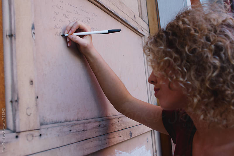young woman writes on wall with pen by Tana Teel for Stocksy United