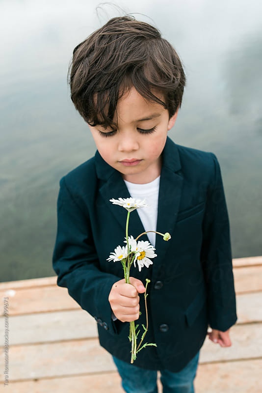 well dressed little boy holding daisies by Tara Romasanta for Stocksy United