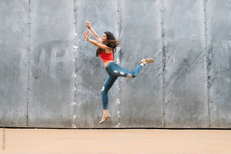 Woman jumping against a wall by Simone Becchetti for Stocksy United