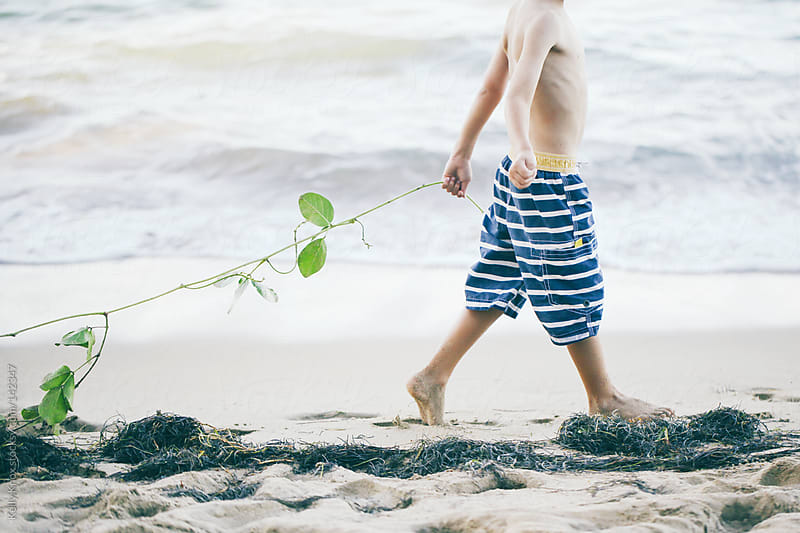 boy pulling a long vine on a beach by Kelly Knox for Stocksy United