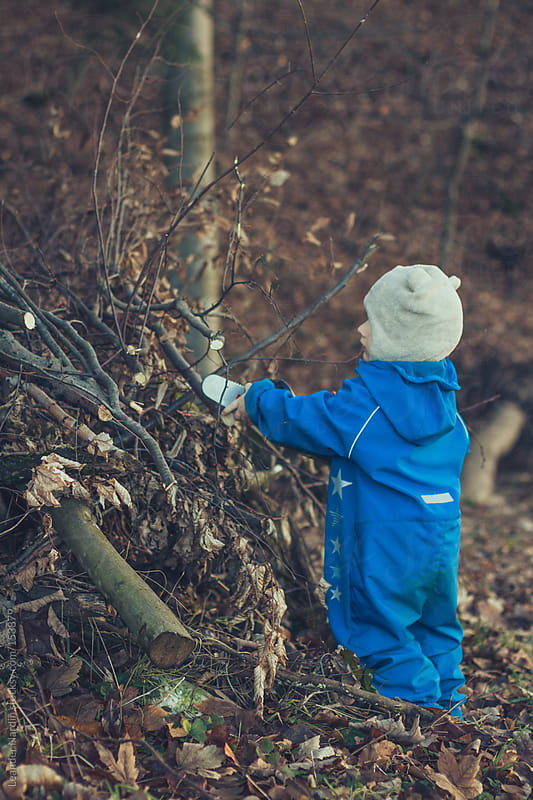 toddler working in the forest with a chainsaw toy by Leander Nardin for Stocksy United