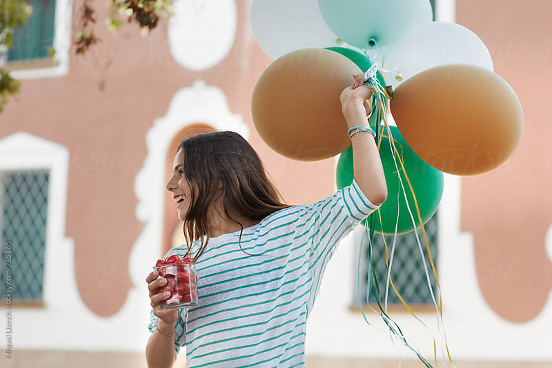 Cute girl with balloons and tomatoes for a party by Miquel Llonch for Stocksy United