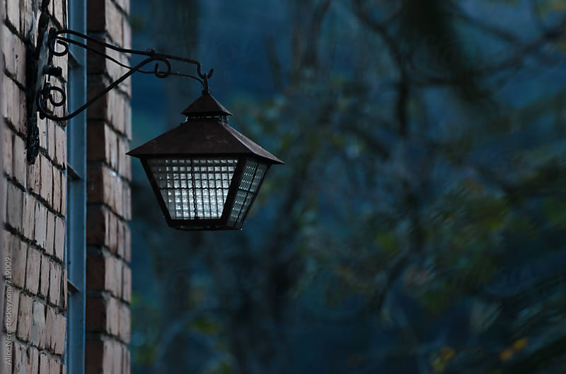 Vintage iron rustic street lamp fixed on a brick wall in dim twilight by Alice Nerr for Stocksy United