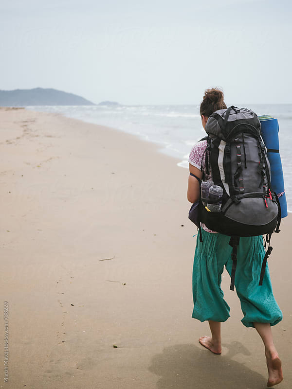 Girl with huge backpack walking on the beach by Martin Matej for Stocksy United