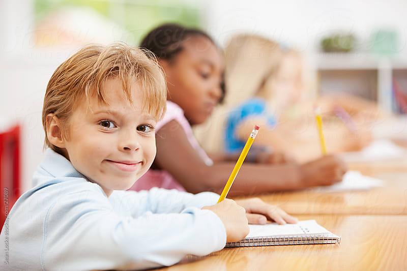 Classroom: Smart Boy Writing in Notebook by Sean Locke for Stocksy United